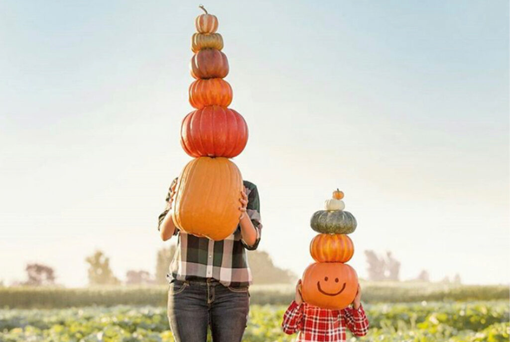 Woman and child holding a stack of pumpkins