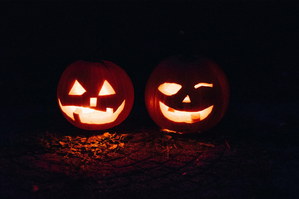 two carved pumpkins glow with goofy faces in the night