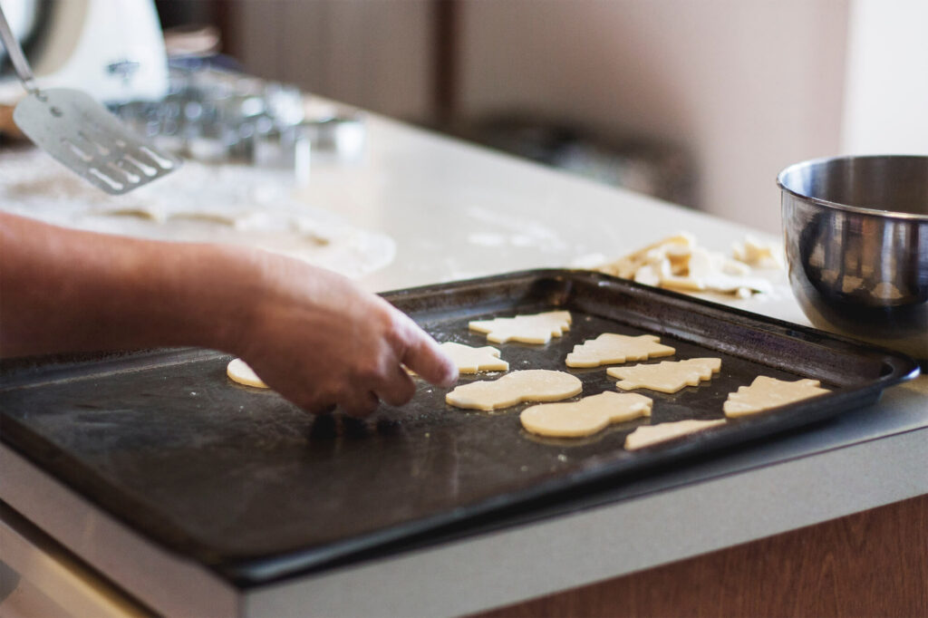Person placing cookie cutouts on a baking sheet while a mess awaits in the background