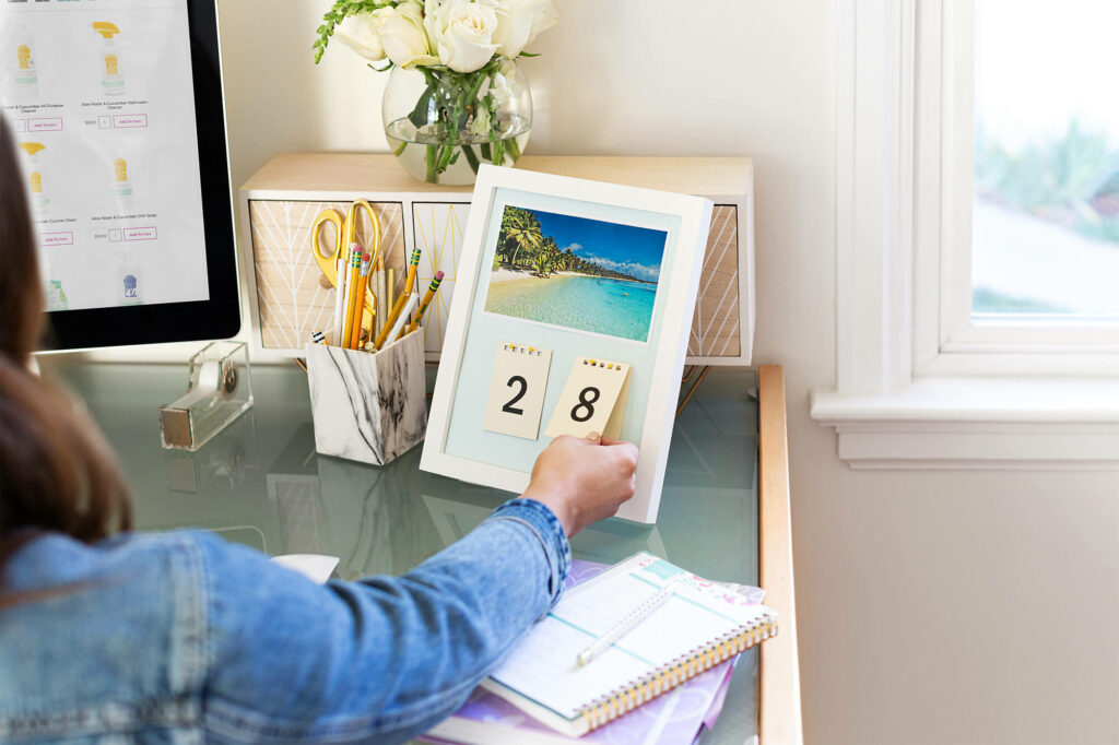 Woman flipping the date on the calendar with Scentsy products pulled up on her computer