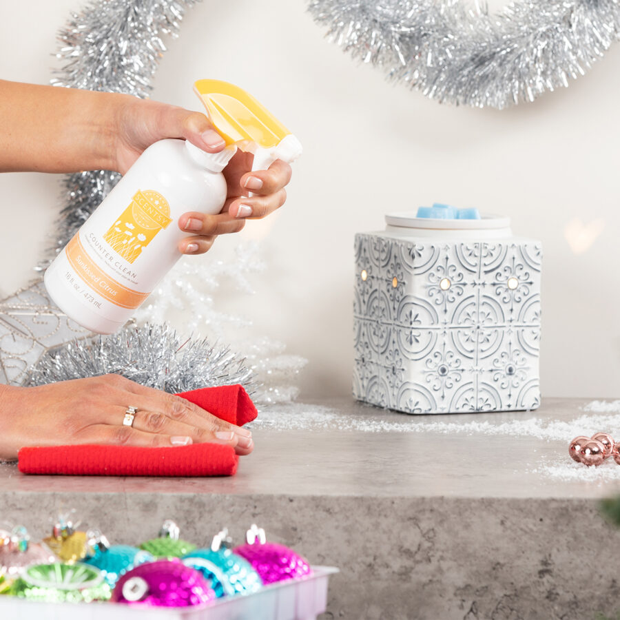 Person cleaning counter with Scentsy's Sunkist Citrus Counter Cleaner featuring the Pressed Tin Warmer in the background