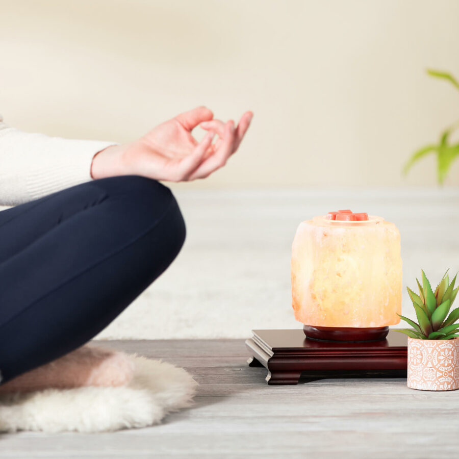Woman meditating near Scentsy's January Warmer of the Month, Himalayan Salt Warmer