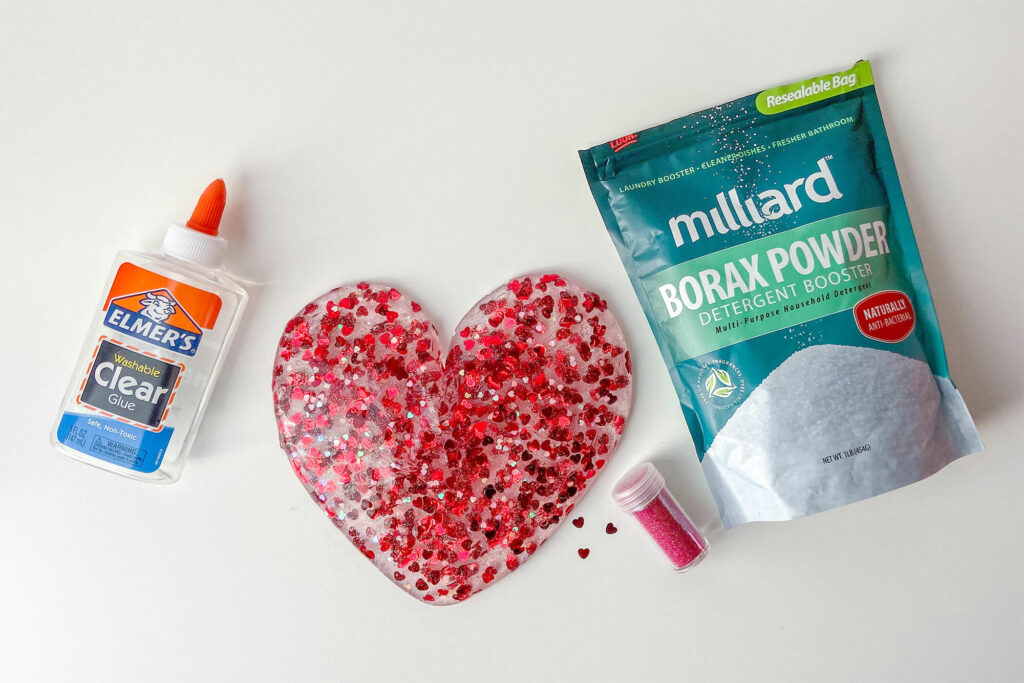 Valentine's Day slime in the shape of a heart surrounded by Elmer's Clear Glue, Borax, and hearts glitter