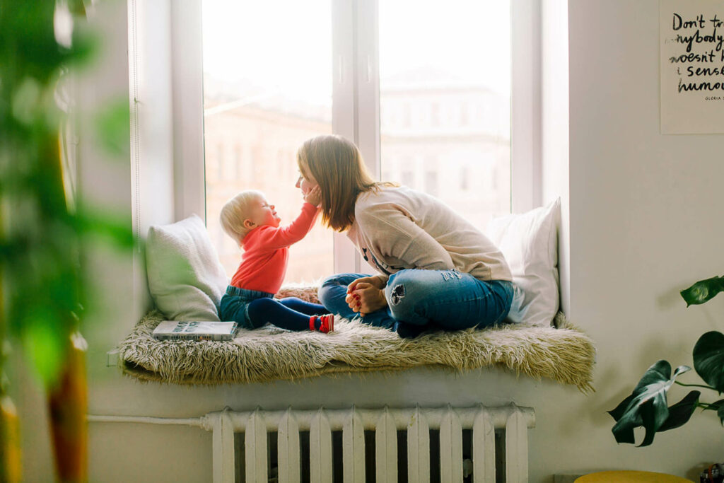 Mother playing with her child on a window sill