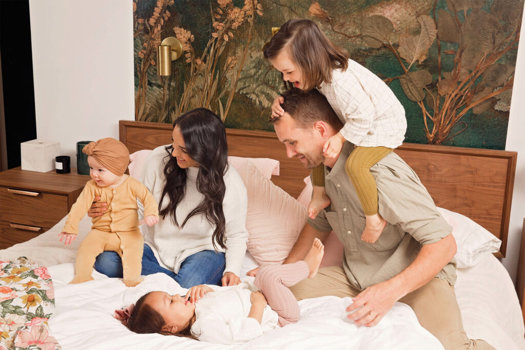 Family of five playing on the parents bed together