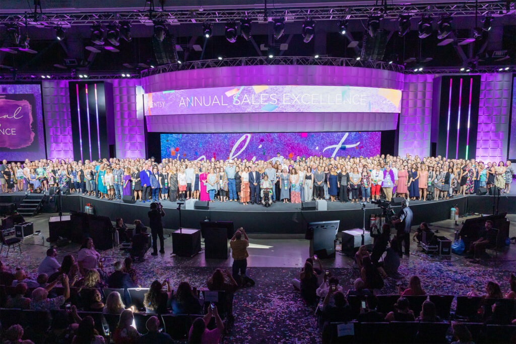 A huge crowd of people on stage with Heidi and Orville during Scentsy Family Reunion