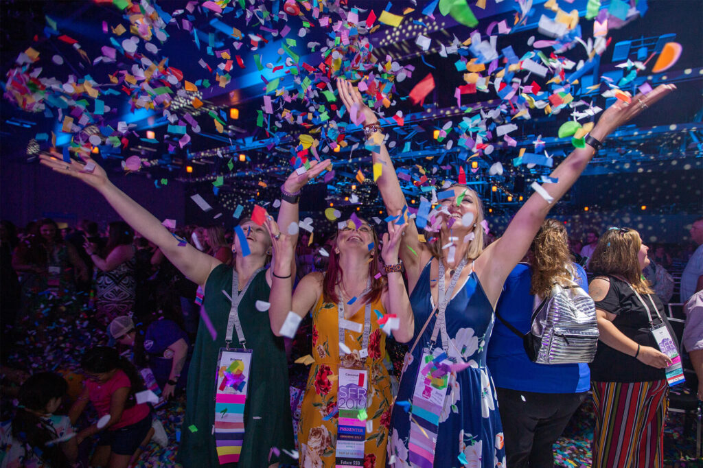 Three women tossing confetti up into the air during Scentsy Family Reunion