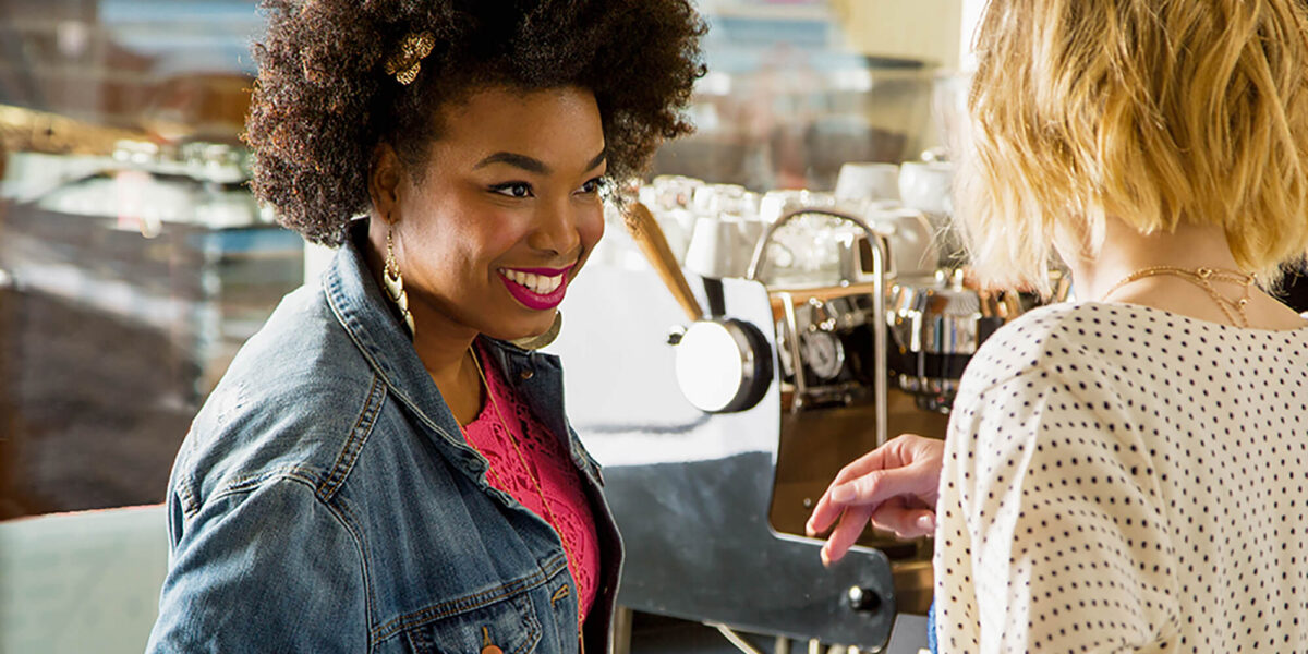 Two women making coffee and smiling