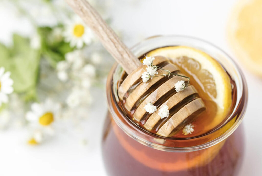 Honey dipper in a small jar of honey with flowers around it