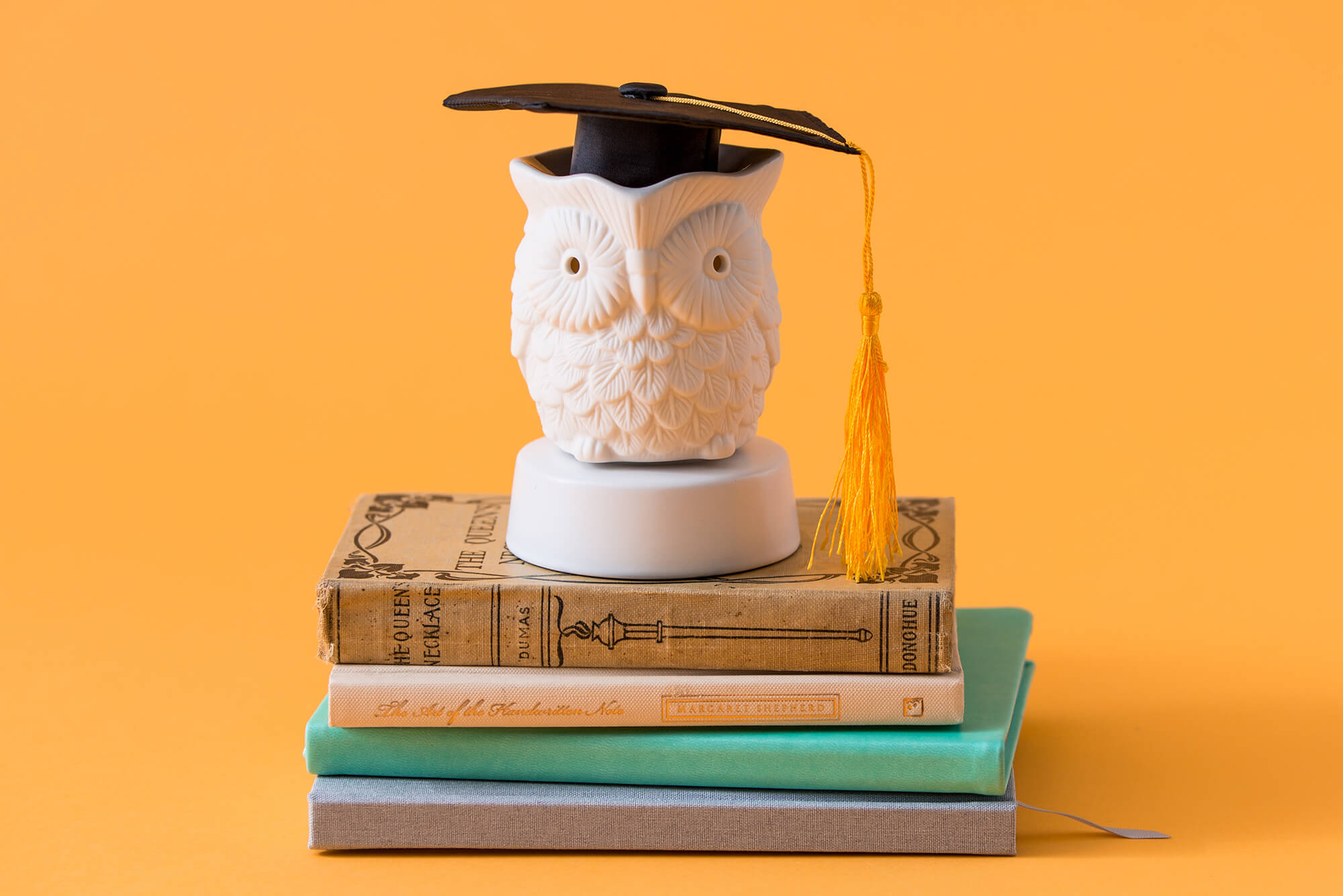 Scentsy Whoot! Mini Warmer on a stack of books with a graduation cap on