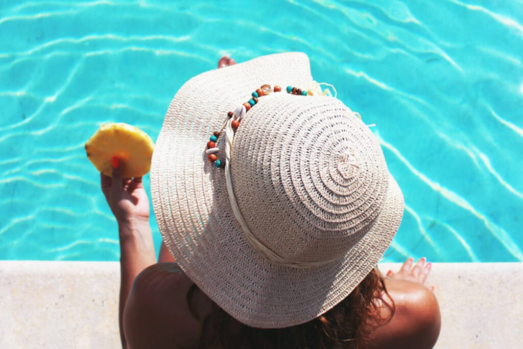 Woman relaxing by a poolside with a slice of pineapple