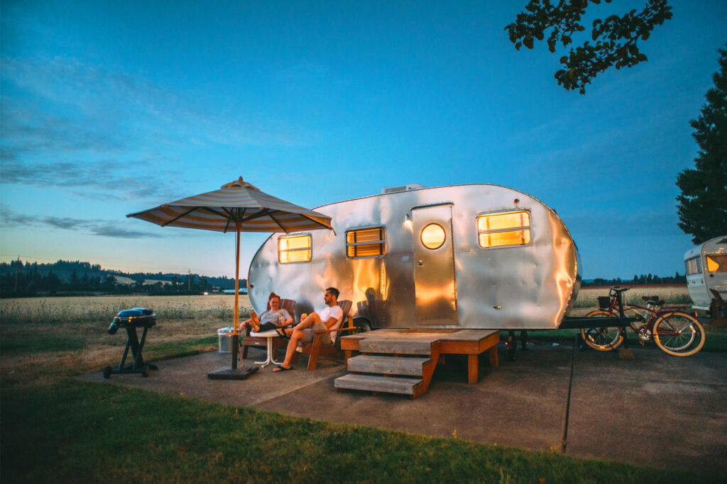 Couple camping outside in a camper enjoying the night sky