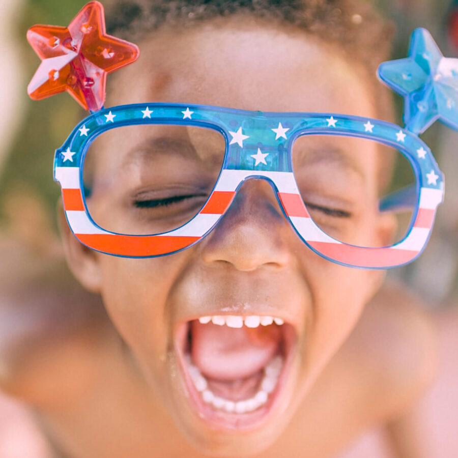 Child happily yelling with American flag glasses adorned with stars