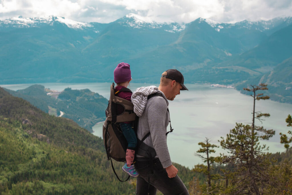 Father and child hiking along trail near big lake