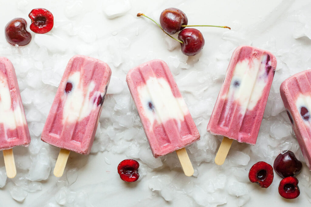 Homemade fruit pops surrounded by cherries