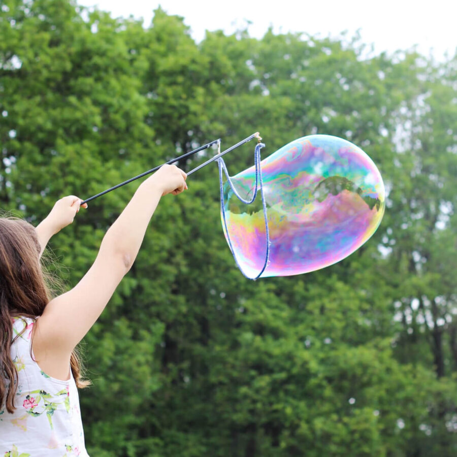 Girl making giant bubble in a park