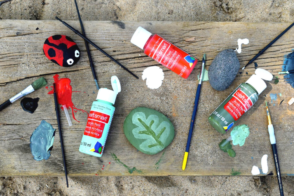Rocks painted to look like a ladybug and a leaf surrounded by art supplies
