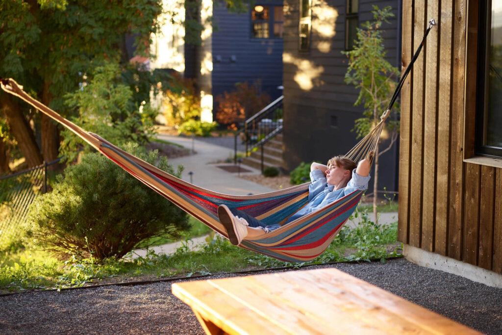 Woman relaxing in a hammock near log house