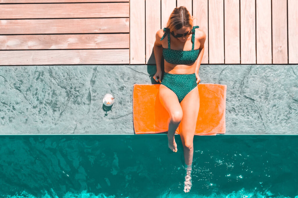 Woman relaxing on the side of a pool
