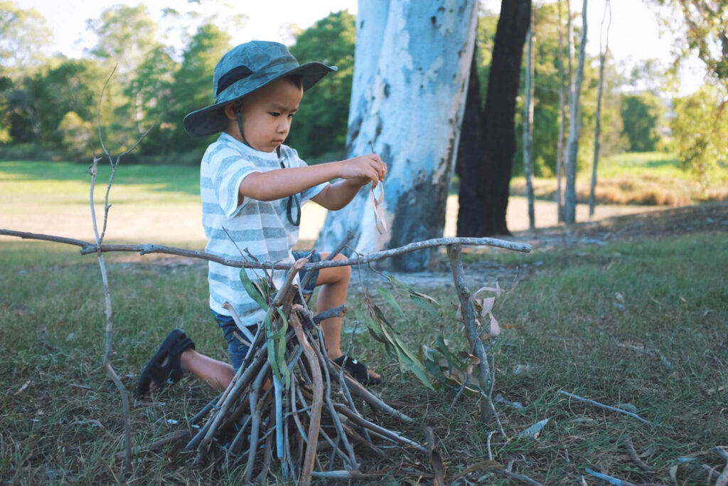 Child playing with sticks to form a teepee