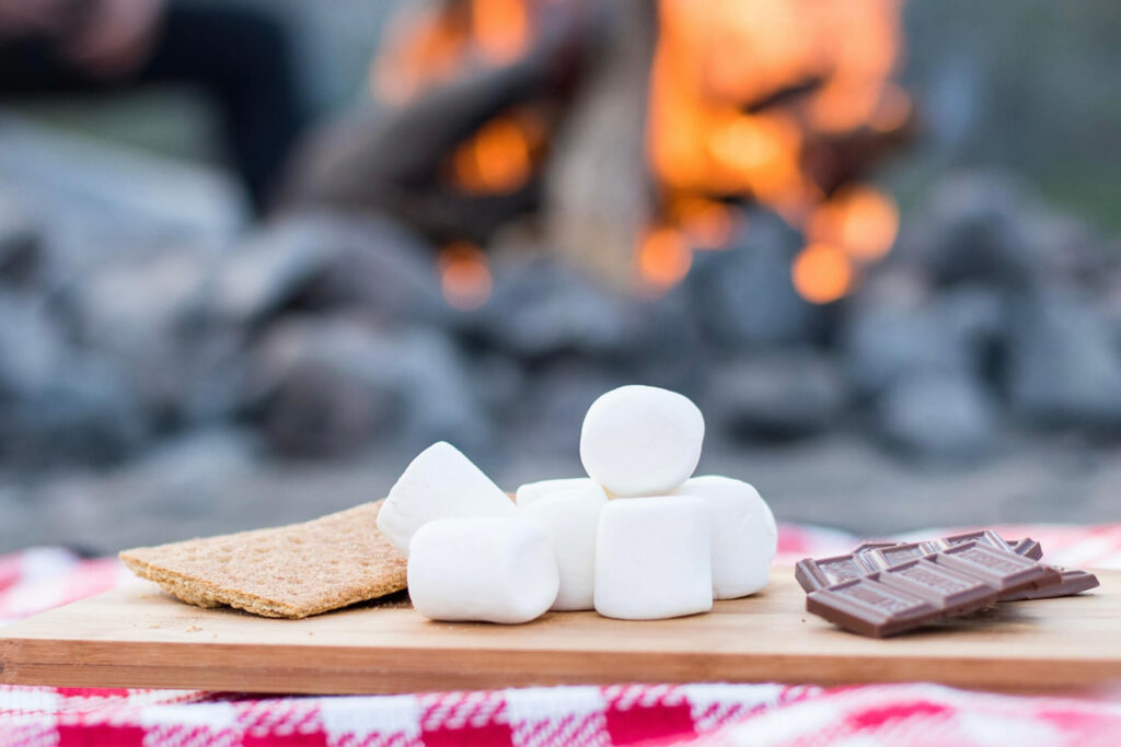 Graham crackers, marshmallows and chocolate on table next to fire