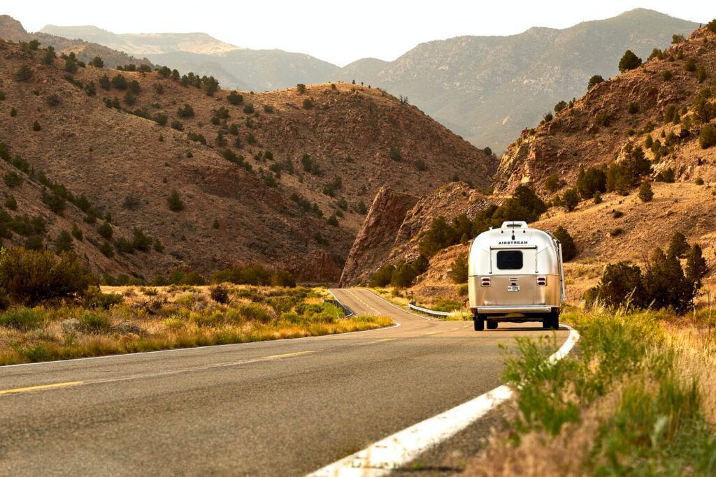 Silver camper driving through mountains