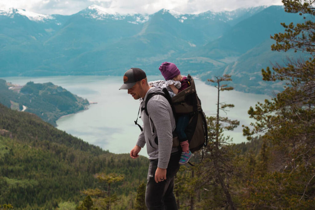 Person hiking in the hills with a child on their back