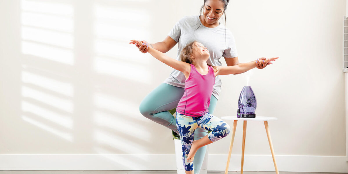Mother and daughter doing yoga with a Scentsy diffuser in the background