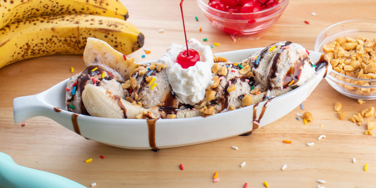 Banana split surrounded by the ingredients