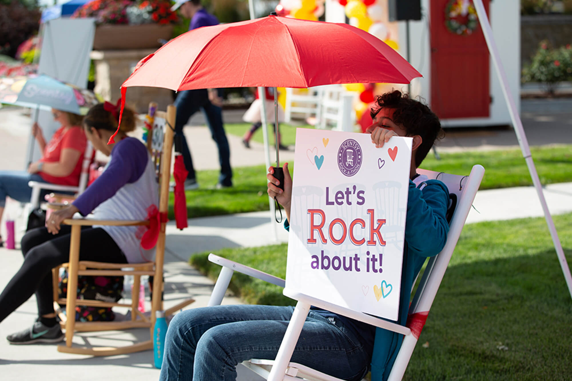 Scentsy Rock-a-Thon person rocking with a hand sign