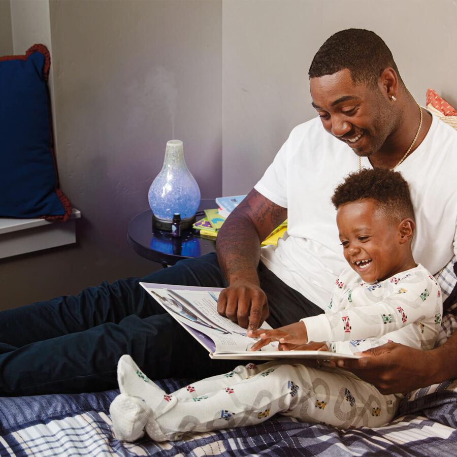 Father reading story to son while laying in bed with a Scentsy diffuser on a bedside table