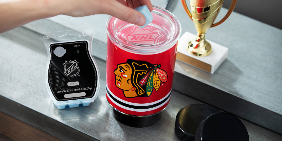 Scentsy NHL Blackhawks mini warmer with Fresh Ice wax with a trophy and hockey pucks nearby