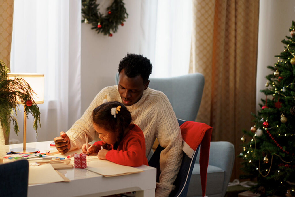 Father and daughter making crafts at a desk