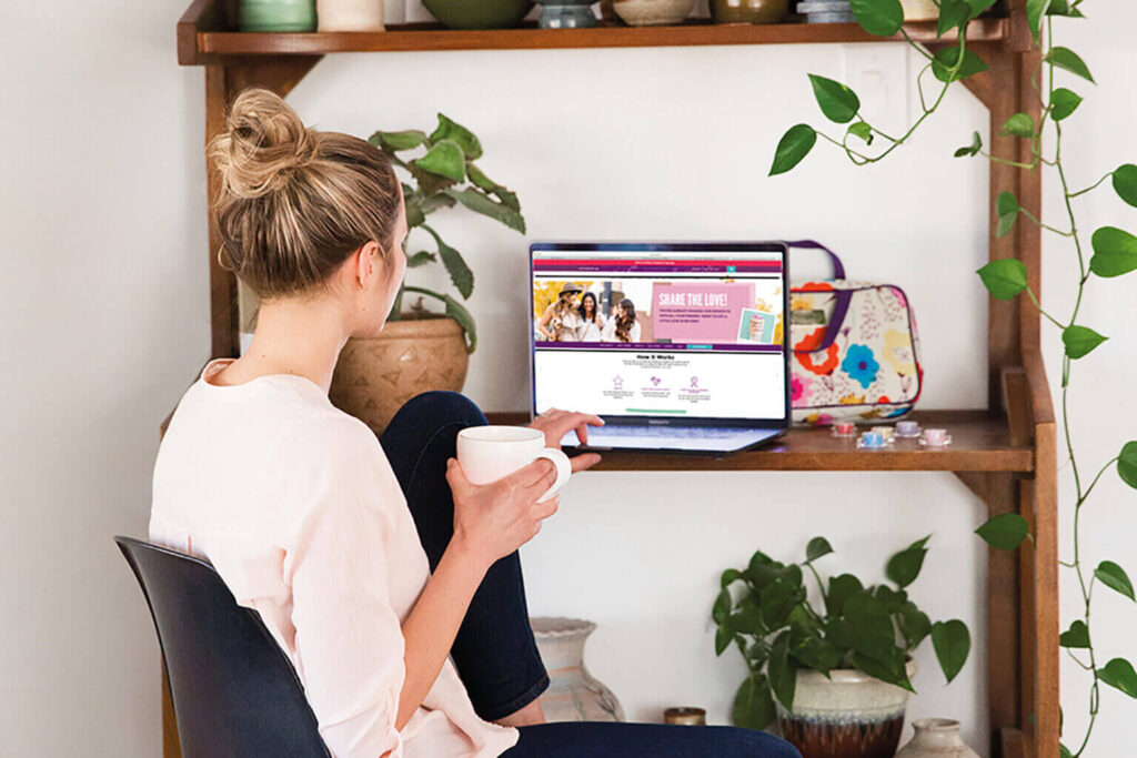 Woman looking at Scentsy home page at desk