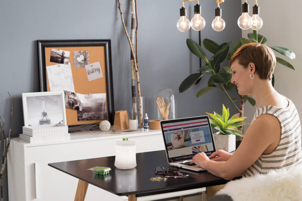 Person looking at Scentsy home page at desk