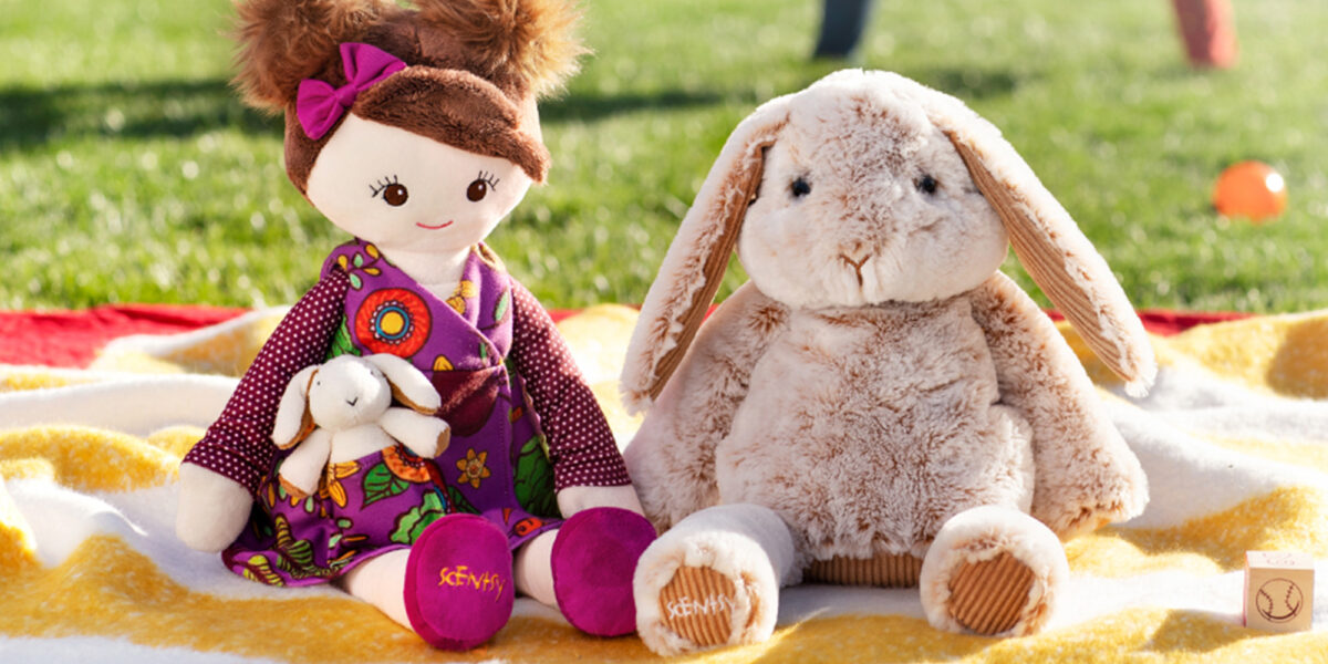 Scentsy Buddies on a blanket outside with people playing in the background