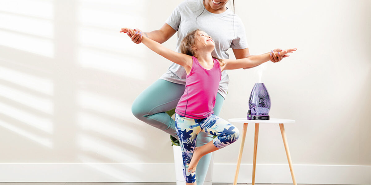 Mother and daughter doing yoga with a Scentsy diffuser in the background on a small table
