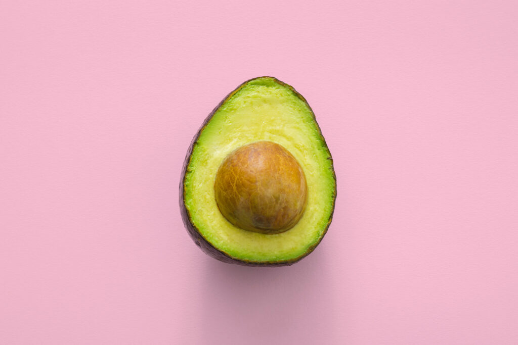 Half of an avocado on a pink background