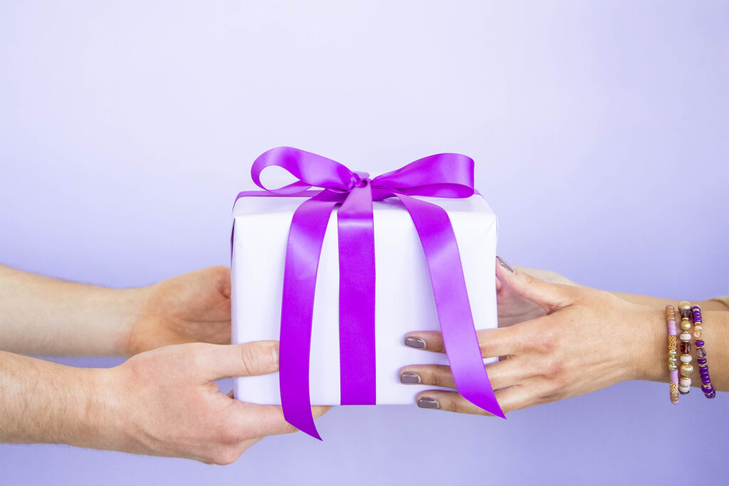 Person handing a gift to another person with a violet background