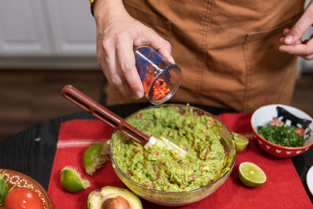 Person making guacamole with ingredients surrounding the bowl