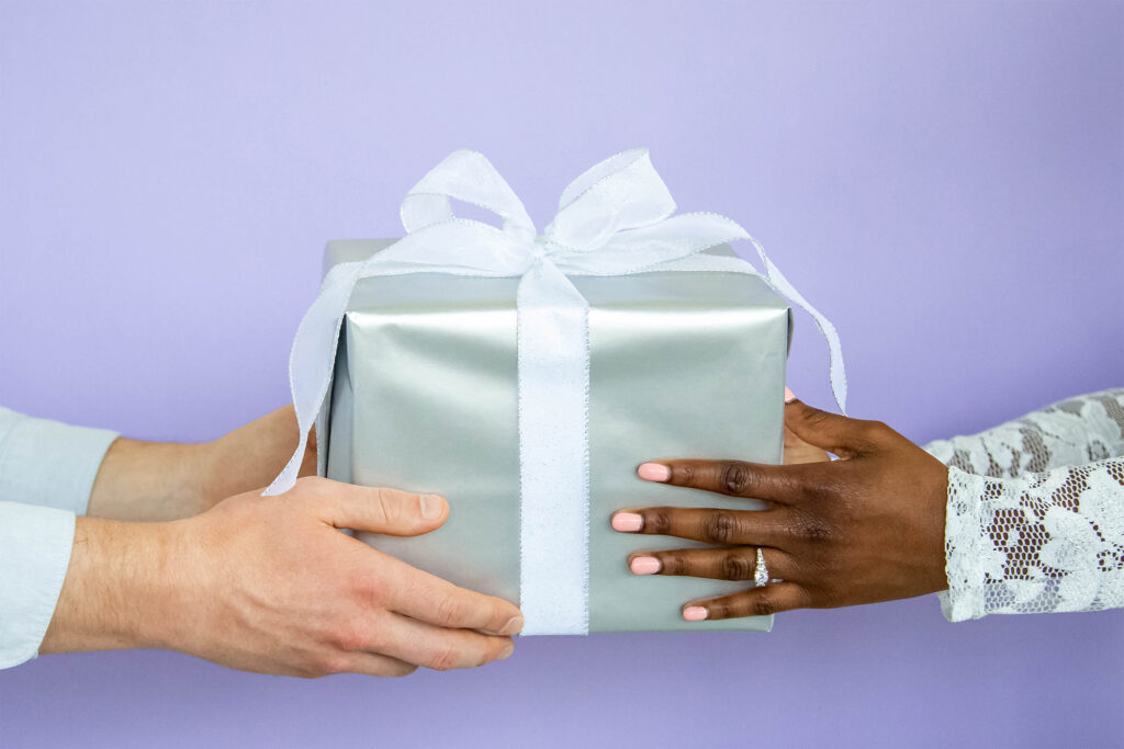 couple holding gift with a purple background