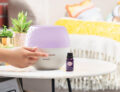 Scentsy's Deluxe Diffuser being switched on by a person off screen on a side table