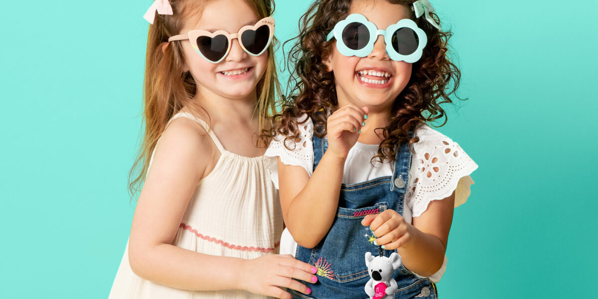 Two girls smiling with sunglasses while one girl holds the new Scentsy Best Friends Buddy Clip