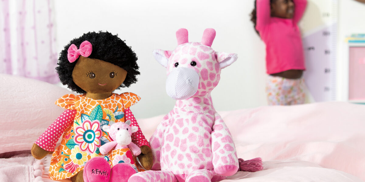 Scentsy Friend Jaya and Scentsy Buddy Genna in the foreground while a child looks at how tall they are in the background