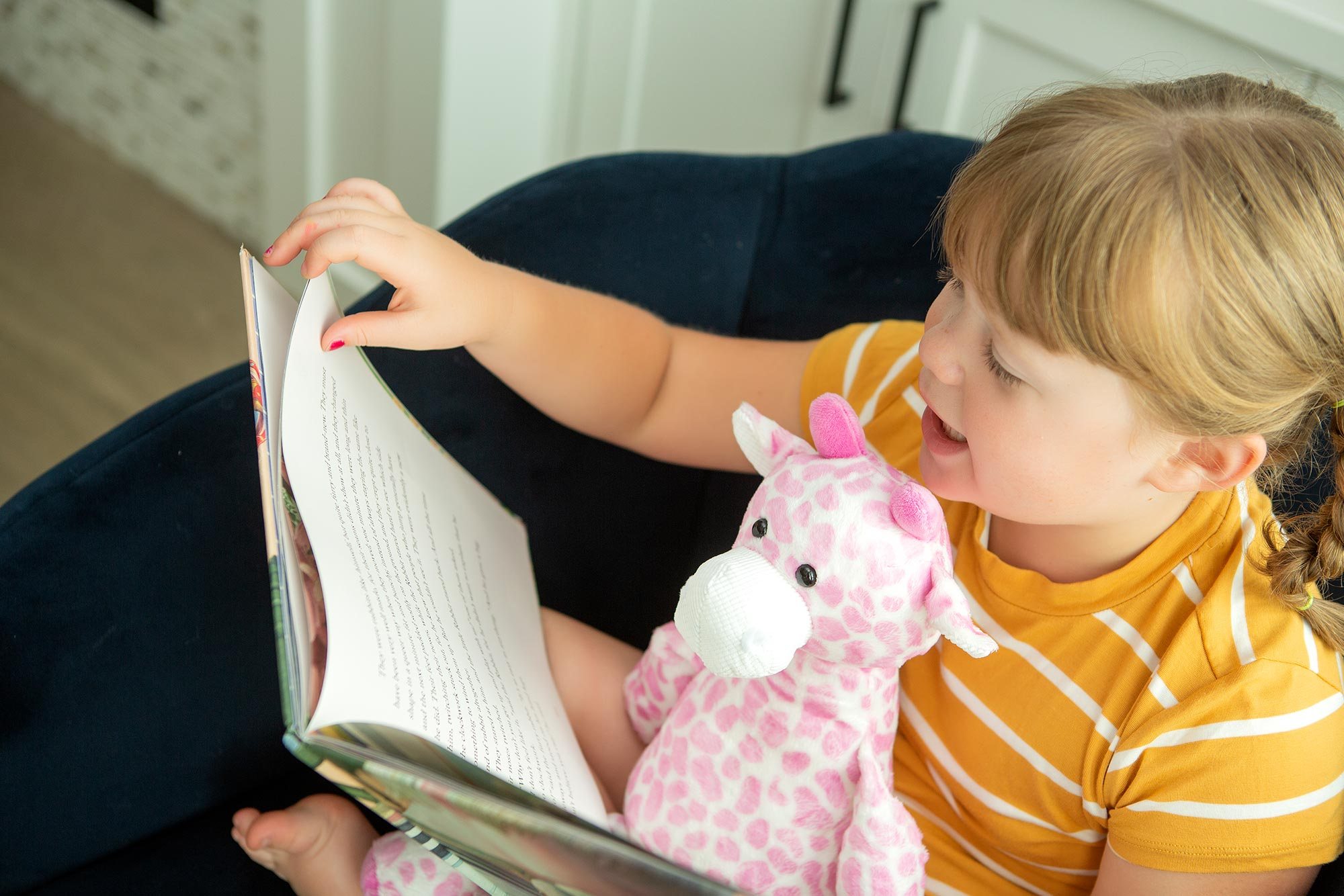 little girl reading book with pink giraffe Scentsy Buddy in her lap