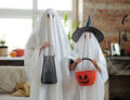 Two people dressed up as ghosts both holding bags for candy