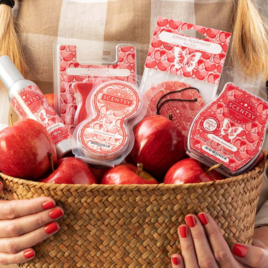 Person holding a basket filled with apples and scentsy red products