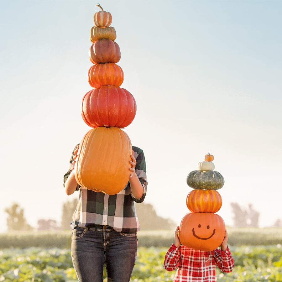 Adult and child holding giant stacks of pumpkins up in-front of their faces