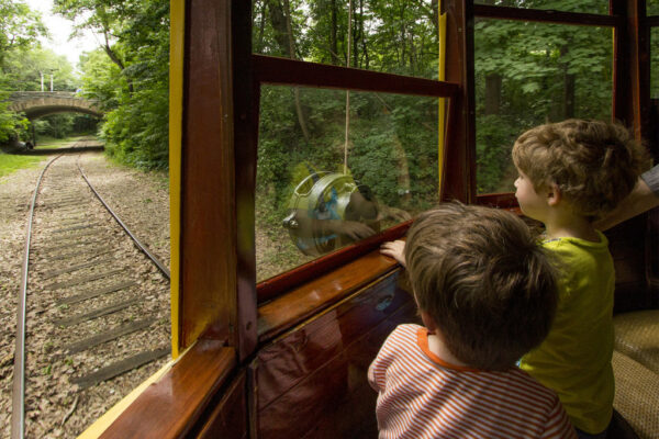 Children and families with thrill aboard the rail line as it passes through the riverfront.