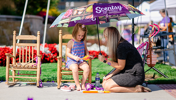 A mother talking to her daughter in a rocking chair.